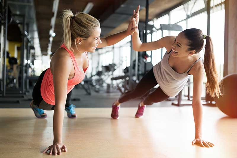 Two women high-fiving during a workout